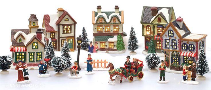 KOMMER SNART IGEN! Flot juleby i porcelæn med 23 dele og lys. Julebyen indeholder 5 huse i gammeldags stil, 7 figurer med personer, en hestevogn, en lygtepæl og 9 træer. Den medfølgende LED lyskæde er ret smart med en stor pæretil hvert hus.
