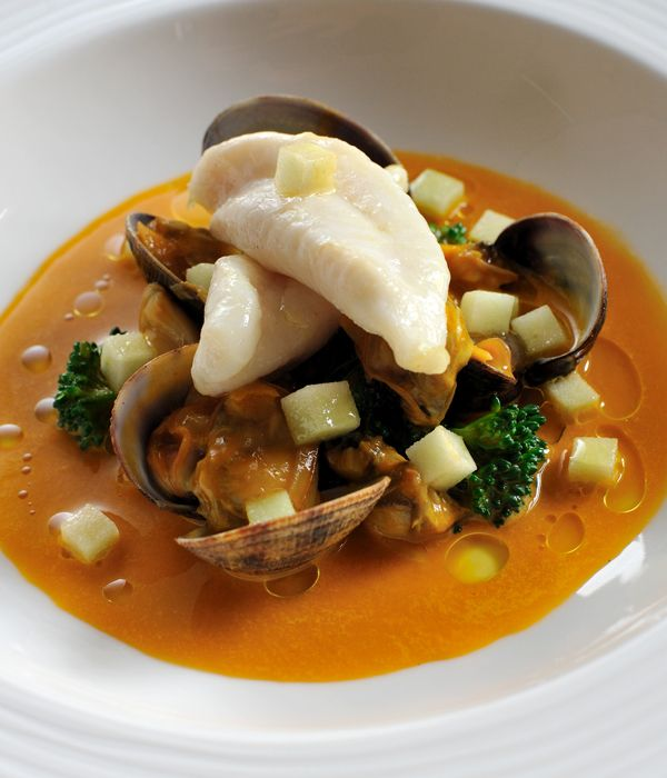 John Dory is grilled and served with a mildly spicy tomato and clam sauce in this Nathan Outlaw dish. This spiced John Dory recipe makes a wonderful spring dinner party dish.