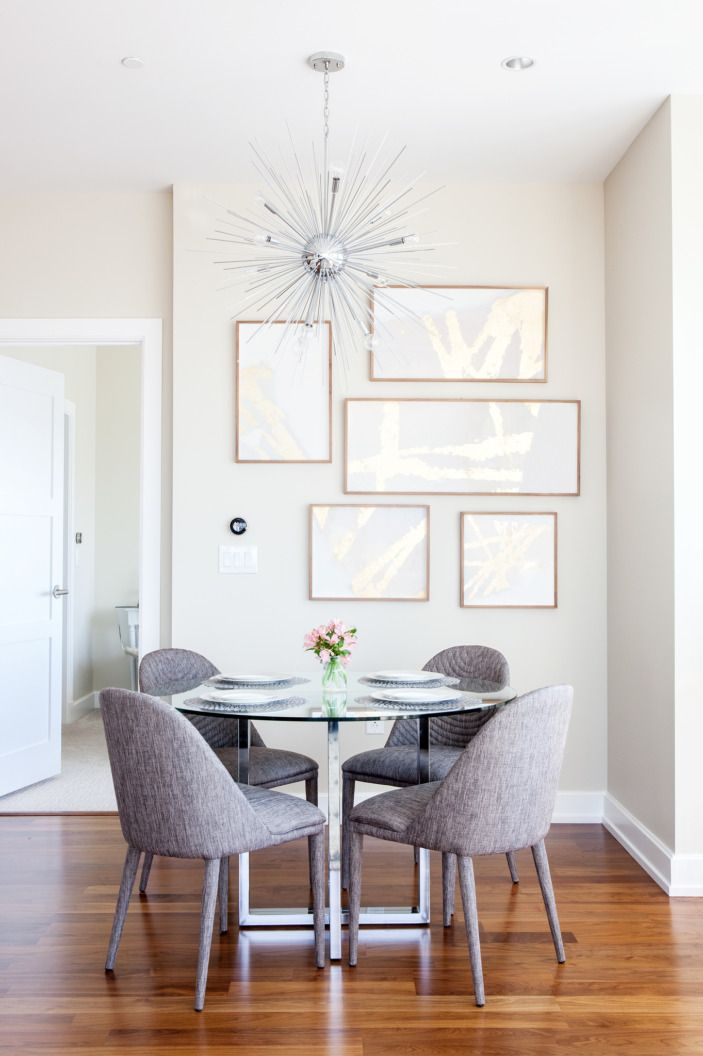 """Our glass-topped <a href=""""http://www.cb2.com/silverado-chrome-47-round-dining-table/s116315"""">CB2 dining table</a> is perfect when friends come over or if it's just the two of us. I had to talk Mike into the sputnik-style chandelier, which I knew would make a statement, but not take up too much visual space. For the record, he loves it now."""