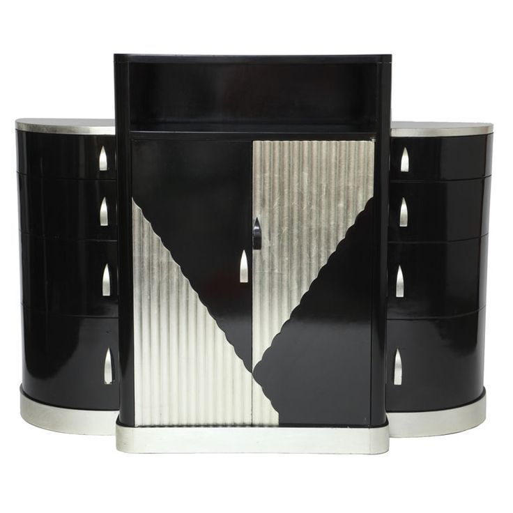 A three-piece dresser cabinet by Paul Poiret. The center cabinet features a shelf and double doors, which reveal four drawers on the interior. It is flanked by side cabinets featuring graduating drawers which rotate to open. Black lacquer with scallop silver leaf design on silver leaf plinth. Pulls are silver leaf wood and are crafted into the cabinet.  This piece is from the estate of the late Dr. Annella Brown.