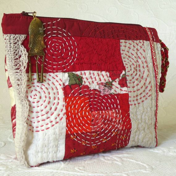 Sashiko quilting highlights the front of this sweet little linen patchwork quilt pouch. Made of linen and cotton repurposed remnants, cute ribbon trim, some crochet lace, and lined with a mens dress shirt striped cotton. A fun gold fish charm for a zipper pull and a loopy handle made of an old necklace braided with red shoelaces. One good sized pocket with funky frayed edges on the back exterior. Measures approximately 10 inches wide by 8 inches high. Sits on a 3 by 7 inch reinforced…