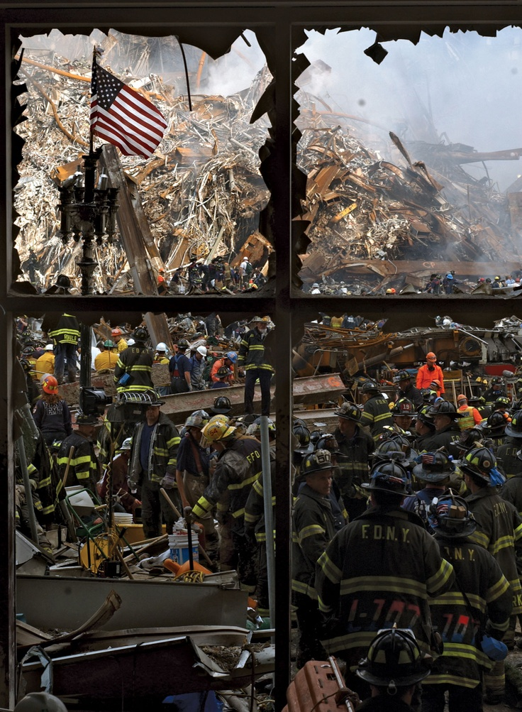 New York City firefighters walking past the American flag at the World Trade Center site in New York City on September 14, 2001, three days after the September 11 terrorist attacks.