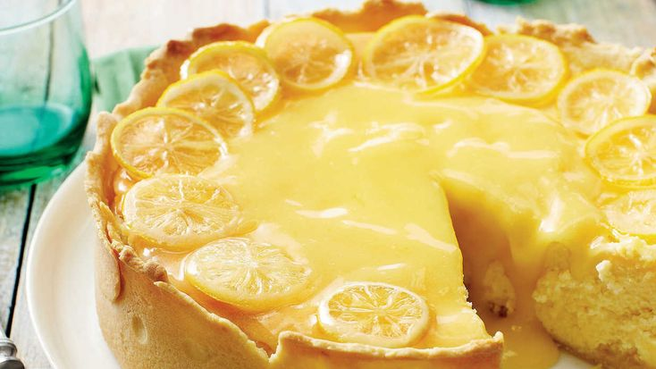 This stunning lemon cheesecake recipe is swirled with plenty of buttery lemon curd and garnished with fresh candied lemon slices.