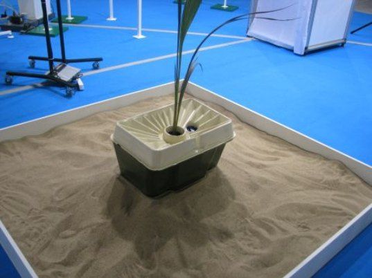 Rainwater and condensation collect in the box's chamber, where water gets trapped. A wick goes into the ground beneath the box, slowly dripping water to the plant's root system everyday. As the plant grows, its roots reach deeper and deeper in the ground, eventually finding their own water source. Once this happens, the box can be removed.
