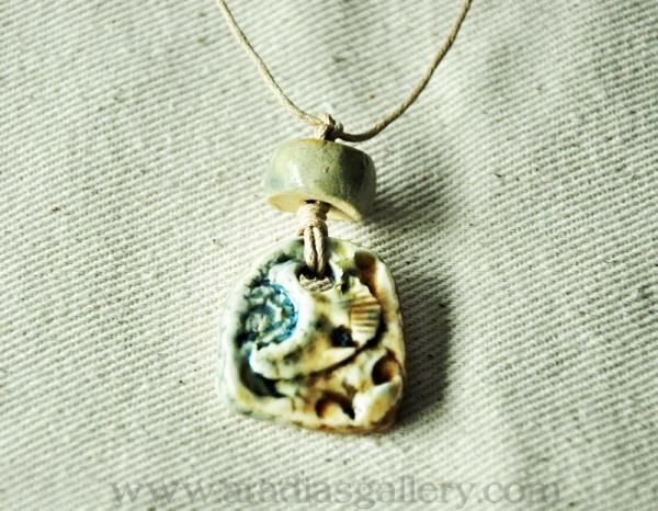 Beachy Boho Glazed Pendant  This original pendant is sure to have you thinking about walks on the beach. The water blue and pale brown make this bohemian style necklace an easy accessory with many color schemes. Wear it with a pair of old jeans as easily as with a flowing dress. The accent bead is also made of glazed stoneware clay.  Aradia Gallery