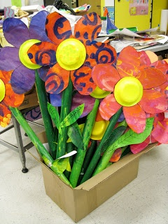 Giant flowers made with painted paper, painted paper bowl centers, cardboard tube stems, and paper for leaves.