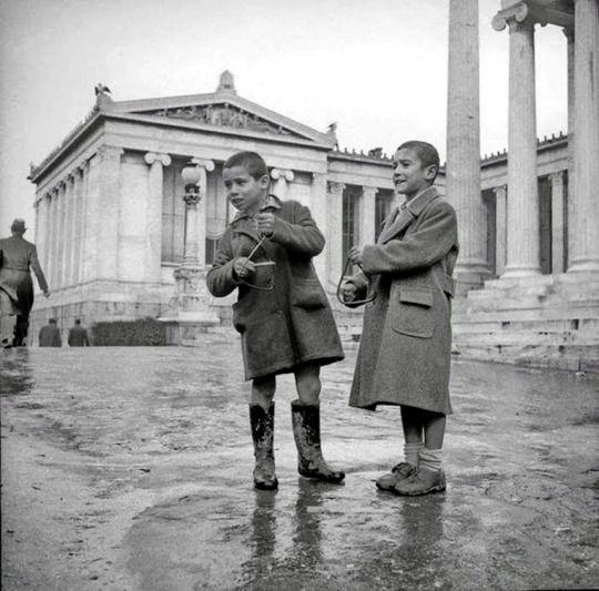 Παιδιά που κρατούν τρίγωνα και τραγουδούν κάλαντα στην Αθήνα του 1950. Λεύκωμα Η άλλη Ελλάδα, 1950-1965 (εκδ. Τόπος 2007).   Φωτογραφικό Αρχείο Κ. Μεγαλοκονόμου