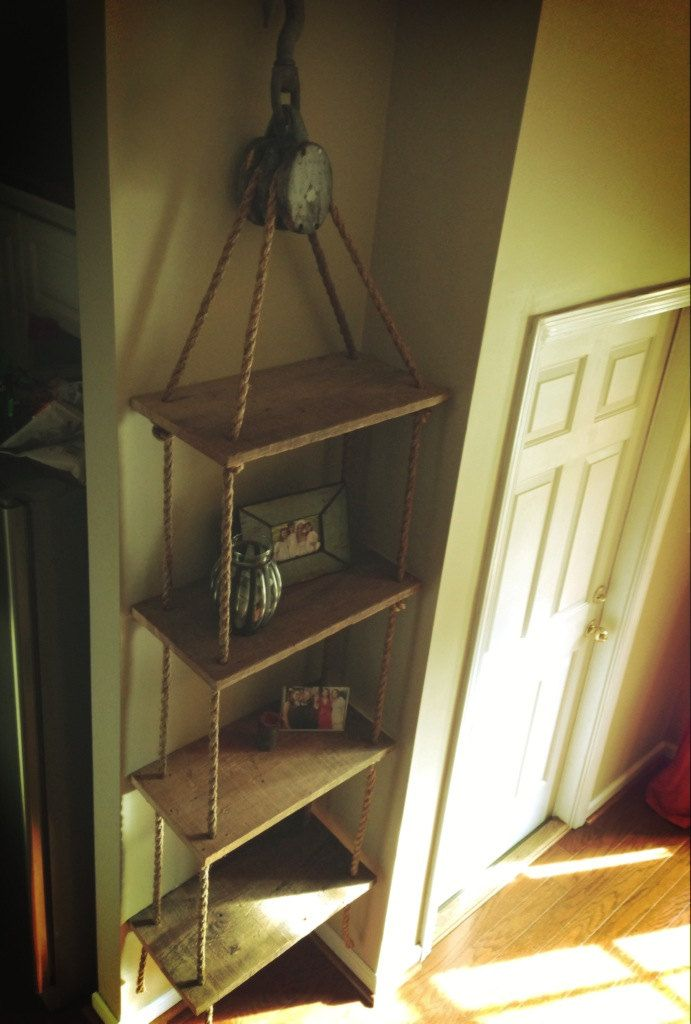 This is a hanging shelf supported by a beautiful antique pulley and manila natural untreated rope.. $185.00, via Etsy.