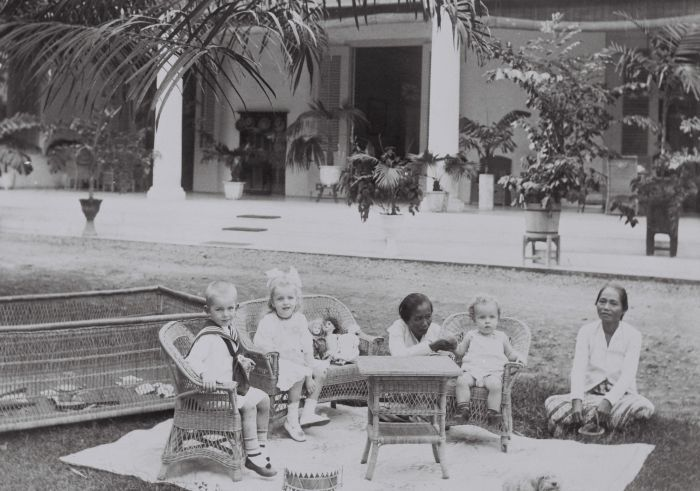 De kinderen van de familie Lonkhuyzen met baboe in de tuin van hun woning in Semarang