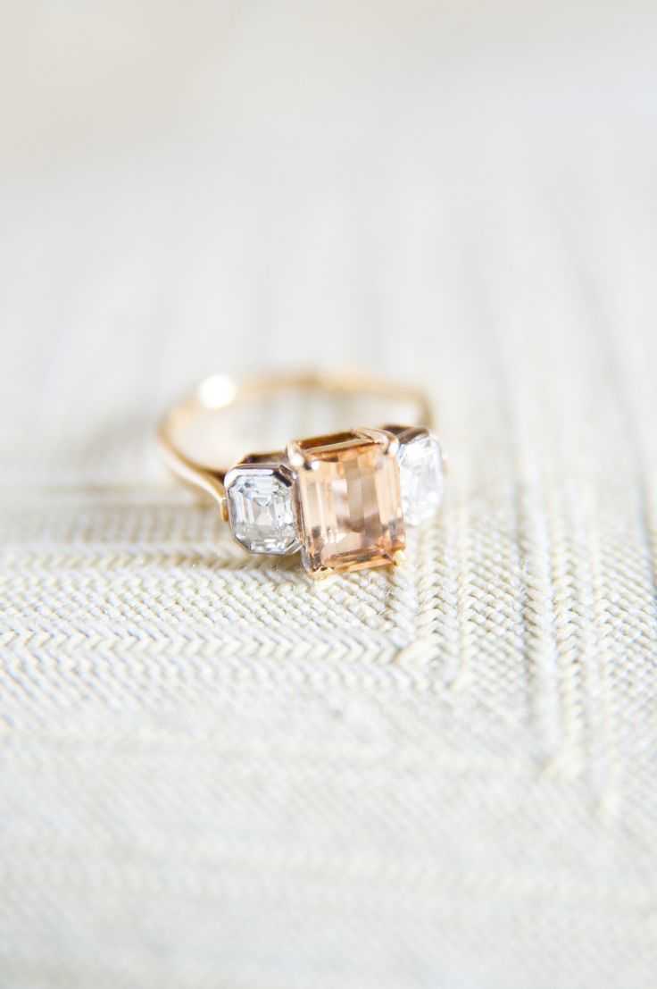 Peach sapphire + yellow gold engagement ring: http://www.stylemepretty.com/2016/04/06/gold-emerald-cut-halo-engagement-ring/