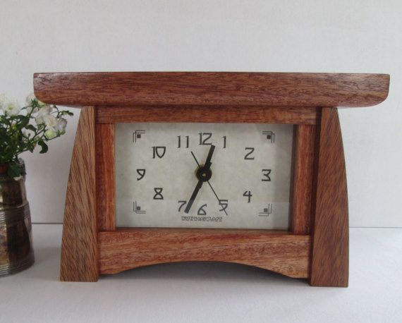 Bungalow Style Mantel Clock made of Mahogany. Rich reddish brown Mahogany with thin streaks of black.  This clock would look great on a fireplace mantel or book shelf and is small enough to go on a desk, coffee or end table.  Made of solid Mahogany. The custom face is printed on Premium Card-stock and protected by a glass front. The clock movement is a quiet continuous sweep (no ticking) quartz with a second hand and takes one AA battery which is included. A removable back is included to…
