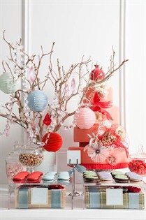 A coral and red cake is the centerpiece of this dessert buffet, featuring colorful Asian-inspired macarons and cookies.