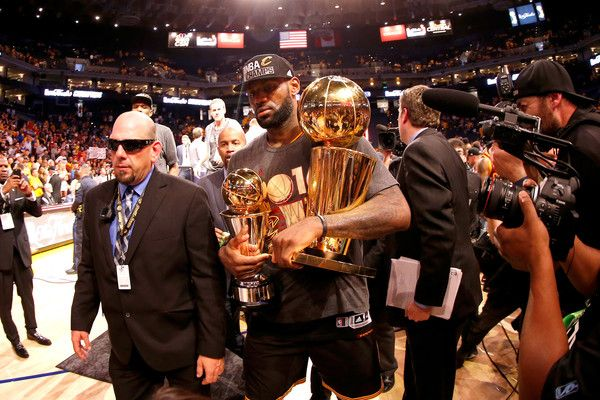 LeBron James Photos - LeBron James #23 of the Cleveland Cavaliers holds the Larry O'Brien Championship Trophy and the Bill Russell NBA Finals Most Valuable Player Award after defeating the Golden State Warriors 93-89 in Game 7 of the 2016 NBA Finals at ORACLE Arena on June 19, 2016 in Oakland, California. NOTE TO USER: User expressly acknowledges and agrees that, by downloading and or using this photograph, User is consenting to the terms and conditions of the Getty Images License…