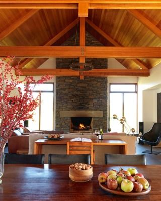 The main living room features warm Victorian ash beams and tongue-and-groove ceiling, schist stonework and the steel of Ambit Stone light fittings from ECC.