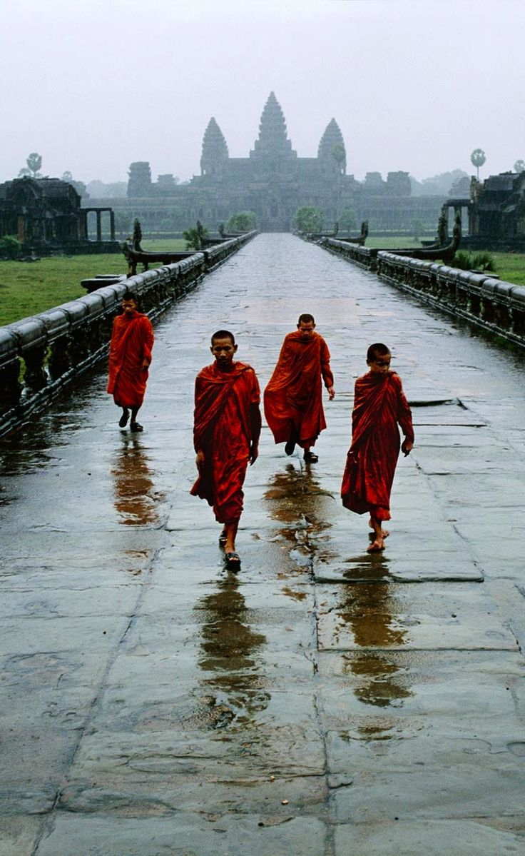 I love this shot of the Cambodian monks walking on the wet pavement after rain is so cool. I love the shot of Angkor Wat in the background too!