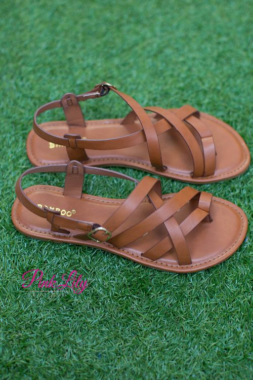 We love these simple and classic sandals - they are an essential for any summer wardrobe! Featuring a cognac color and a gold colored buckle on the side, these sandals are perfect for all of your summer adventures.