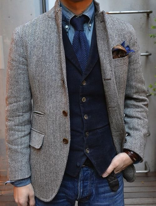 Shop this look on Lookastic:  http://lookastic.com/men/looks/denim-shirt-and-tie-and-pocket-square-and-waistcoat-and-blazer-and-jeans/4008  — Blue Denim Shirt  — Navy Knit Tie  — Brown Paisley Pocket Square  — Navy Corduroy Waistcoat  — Grey Herringbone Wool Blazer  — Blue Jeans