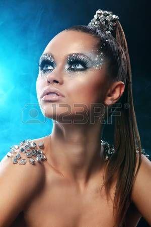 Portret van vrouw met artistieke make-up en strass opzichte van het achtergrondniveau photo