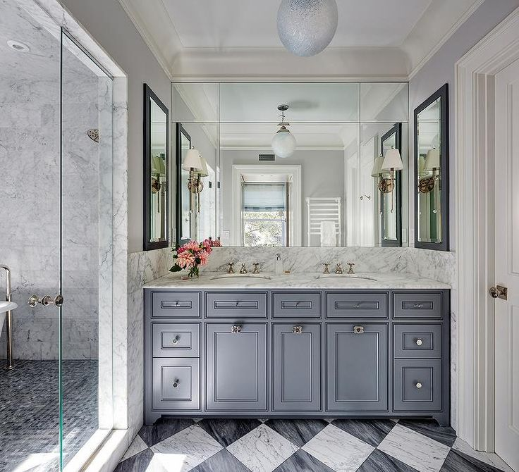 white and gray harlequin floor tiles lead to a steel gray dual washstand fitted with geometric knobs and a white marble countertop holding his and her sinks