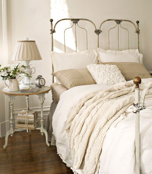 This antique cast-iron bed sports a cable-knit throw from the Martha Stewart Collection and a duvet cover by French Laundry Home. An Anthropologie teacup lamp sits atop the turned-leg nightstand.   - CountryLiving.com