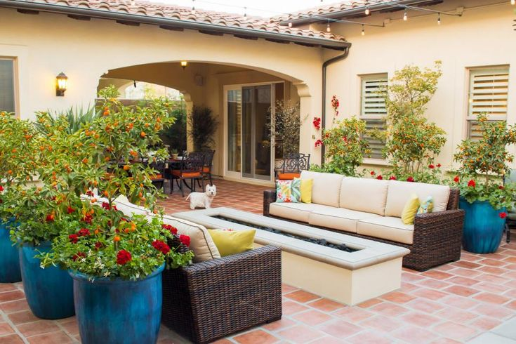 A pair of welcoming outdoor sofas flank a long, narrow fire pit in this Tuscan-inspired California courtyard, inviting conversation. Lush plantings grace containers throughout the space, adding to its warmth and charm.