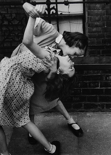 Energia y buen humor en East End - Londres (1954) y es obra de Godfrey Thurston Hopkins, un pintor y fotógrafo inglés (nacido en Londres en 1913) conocido principalmente por sus imágenes de la Inglaterra (principalmente Liverpool) de los años 50, desde escenas de la vida cotidiana en los suburbios hasta imágenes espontáneas de las estrellas de cine.