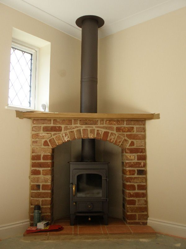 Clearview Pioneer 400 wood burning stove with brick and beam corner fireplace and twinwall fluepipe.