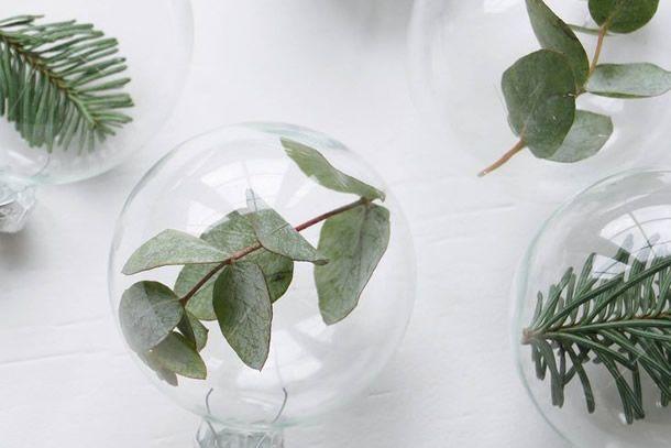 ideias de natal nórdico e rústico com bolas de natal transparentes com folhagens.