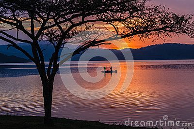Early morning dam water color landscape glass reflections with bass fishermen in boat