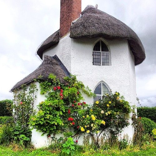 How quaint! Storybook house with arched leaded windows and thatched roof Toll House. Stanton Drew.