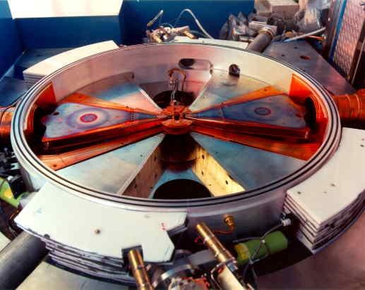 Cyclotron: Vue intérieure d'un cyclotron d'isotopes médicaux montrant les structures électromagnétiques permettant une accélération, les particules formant une spirale à partir du centre. Image offerte par TRIUMF.