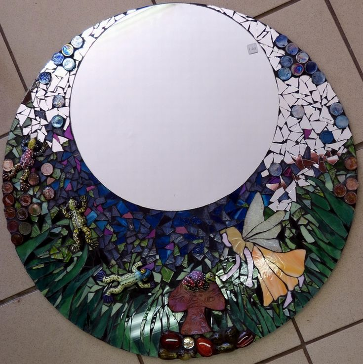 Mosaic mirror, mixed media I absolutely love this mirror! I love the idea of the fairy garden and using a variety of different elements. The fairy I drew onto colored glass & cut out using a scorer. I then nipped the glass to shape. The grass I painted onto the board with acrylic paint and then cut clear glass.  The frogs I made from clay, glazed and fired in a kiln and the toadstool is Fimo clay. The rest of the elements are glass pebbles and different mosaic tiles