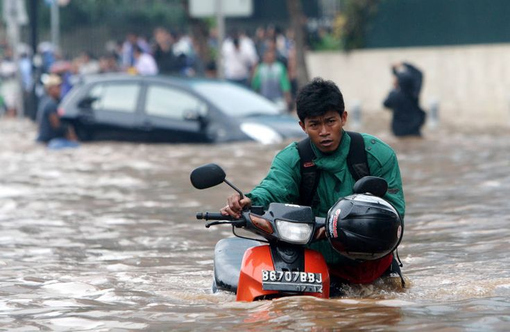 A man pushes his motorcycle through a flooded street in Jakarta, Indonesia, Thursday, Jan. 17, 2013. Floods regularly hit parts of Jakarta in the rainy season, but Thursday's inundation following an intense rain storm appeared especially widespread. (AP Photo/Tatan Syuflana.)