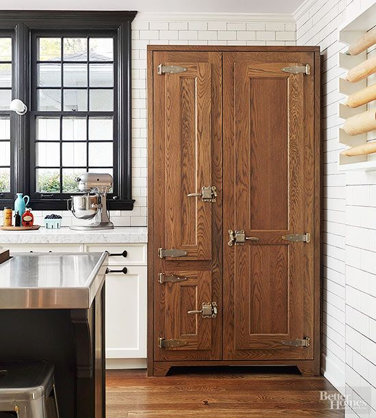 With an icebox profile and vintage latches, this nostalgic pantry underscores the kitchen's farmhouse character. Three different doors add interest on the cupboard's face; the doors open to abundant compartmentalized storage that makes it easy for the homeowners to put their groceries away in a well-organized manner.
