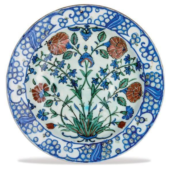 IZNIK (ANATOLIE -TURQUIE) Plat aux tiges de jacinthes Plat (tabak) en céramique à pâte siliceuse à bord uni. Décor peint en polychromie bleu, rouge et vert sur fond blanc sous glaçure transparente incolore,… - Tessier & Sarrou - 14/10/2015