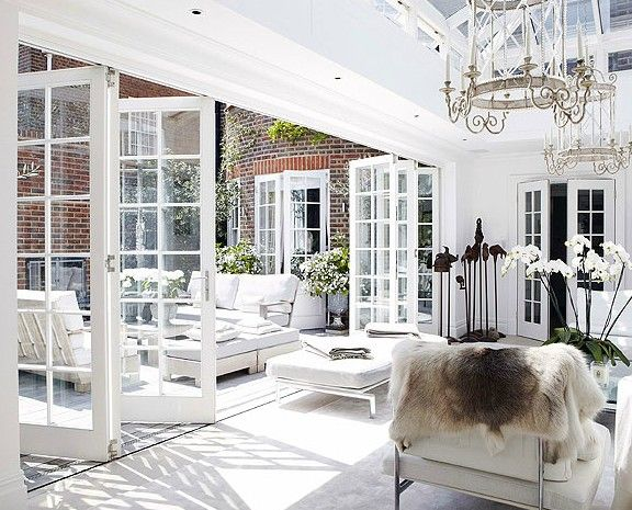 Paned glass window wall opening to a furnished terrace. Chandeliers. Orchids. Beautiful bright natural light. Textures.