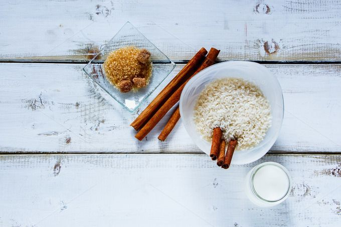 #Ingredients for making rice pudding  Kitchen table with ingredients for making rice pudding. Bowl of white uncooked rice brown sugar cinnamon sticks and jug of milk or cream over old wooden background. Top view space for text
