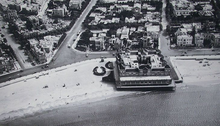 Vista aérea de la playa y el barrio de Pocitos. En primer plano el Hotel de los Pocitos. Arriba, a la derecha, puede apreciarse el edificio del Palace Hotel Pocitos.  El Hotel de los Pocitos comenzó a construirse en el año 1912, según proyecto del arquitecto inglés —residente en Montevideo— John Adams, luego de que un incendio destruyera el primer edificio. Si bien era frecuentado por familias uruguayas, la mayoría de sus huéspedes eran argentinos, lo cual era coherente con la política…