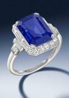 An Art Deco sapphire and diamond ring, by Cartier, circa 1930. The cut-cornered step-cut sapphire, weighing 5.34 carats, within a surround of single and baguette-cut diamonds, mounted in platinum, signed Cartier London, numbered, maker's case. #Cartier #ArtDeco #ring