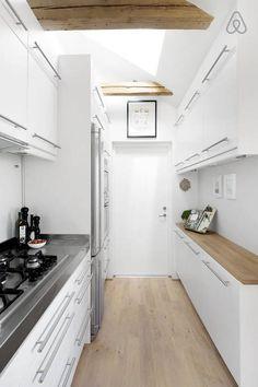 Toute en longueur, cette cuisine présentait la difficulté de devoir être accessible des deux côtés. Deux plans de travail se font donc face, pour une bonne circulation dans l'espace. Les meubles occupent toute la hauteur disponible. Sur le mur de droite, les placards bas ont une faible profondeur pour dégager la circulation. Une bien jolie décoration blanche, métal et bois en provenance d'Ikea, pour cette petite cuisine !