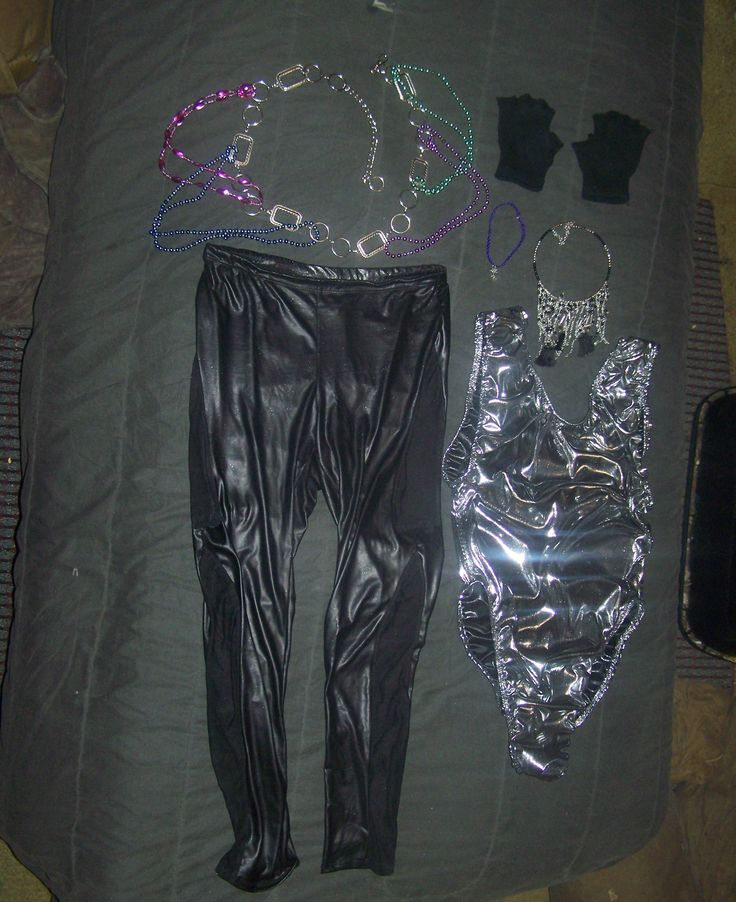 This is the outfit I wore when going out clubbing and having a good time with friends!  The items in this outfit include a pair of shiny black latex spandex leggings with gothic shaped fishnet panels on the sides, a shiny liquid silver lame' one-piece leotard bodysuit, a silver chain belt with attached colorful beads on it, a silver necklace with hanging silver and black things, a goth-style purple necklace with a little silver dragon emblem on it, and a pair of black fingerless gloves…