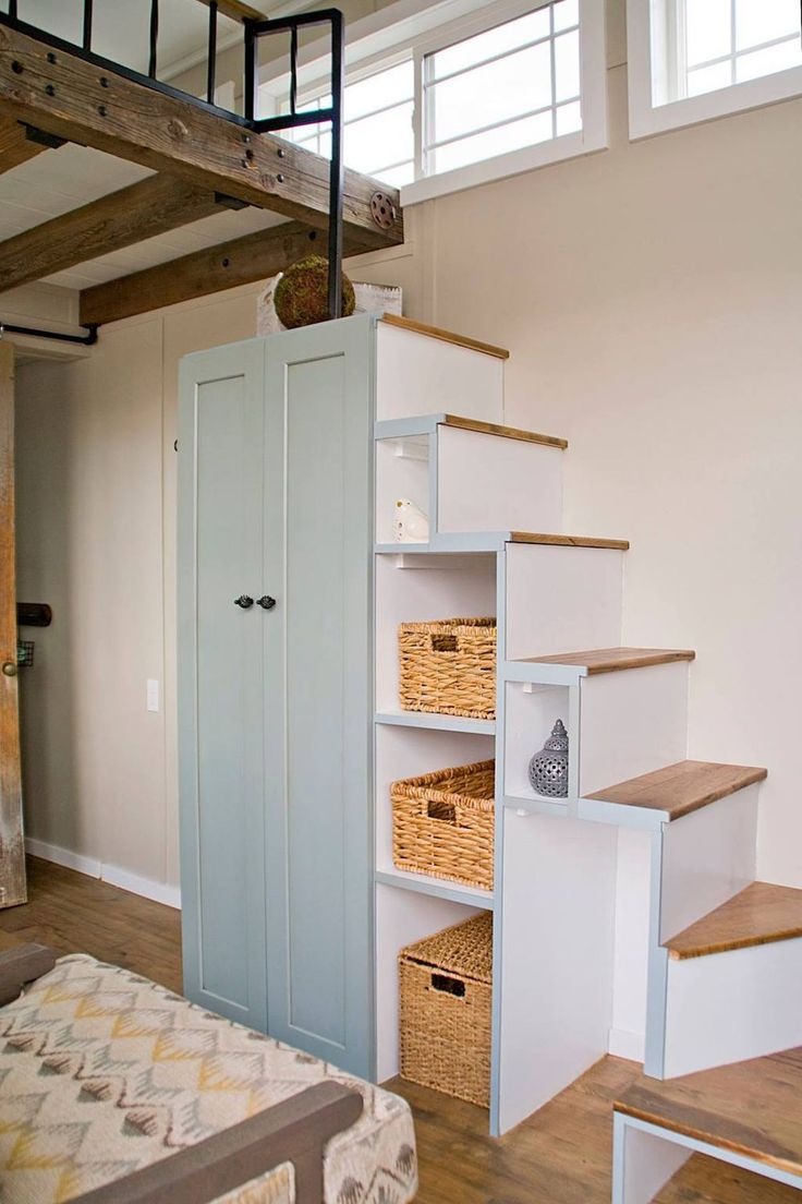 Tiny house with staircase that has storage and sleeping platform.