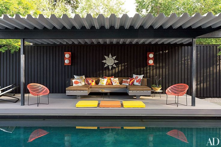 Jonathan Adler and Simon Doonan achieve contemporary cool at their Shelter Island pool pavilion with a mod sectional sofa and array of colorful pillows.