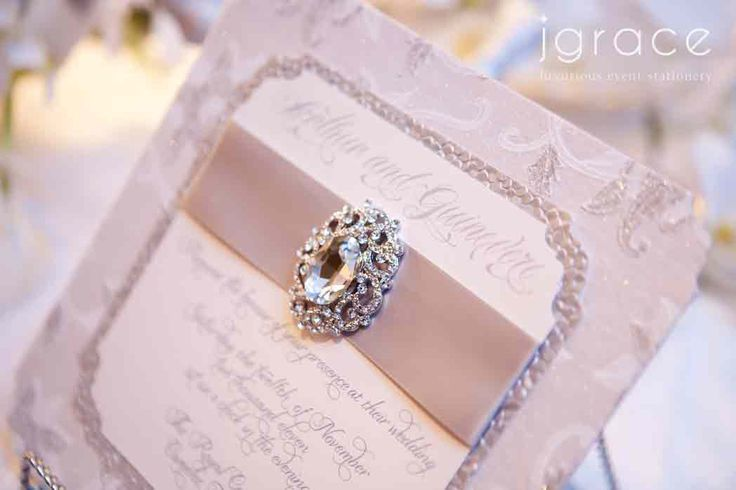 luxurious winter wonderland wedding invitation featuring a vintage inspired crystal brooch and handmade papers. by j grace