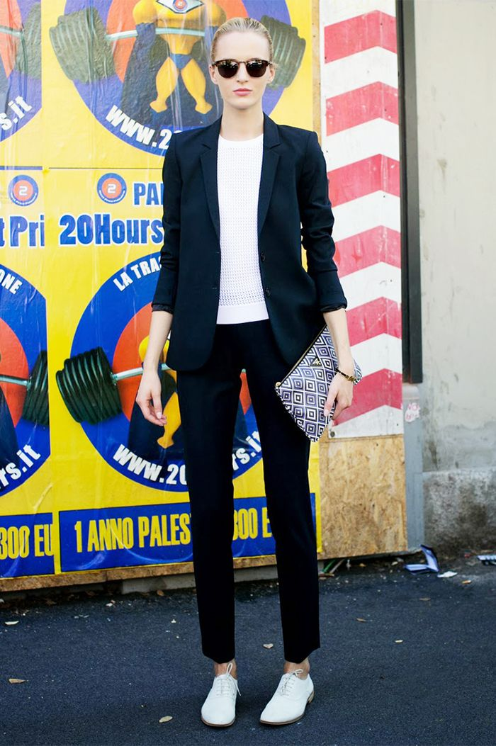 A black suit is paired with a white shirt, printed clutch, sunglasses, and white oxford shoes