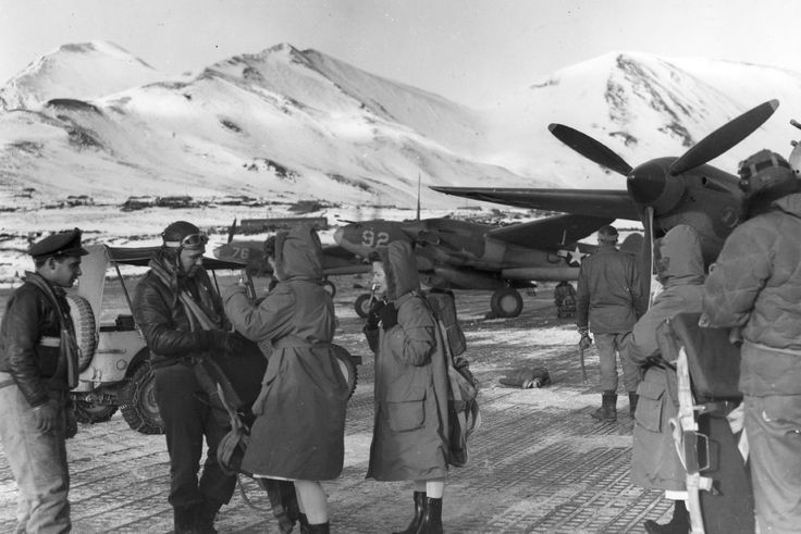 Members of the USAAF 54th Fighter Squadron with some Army nurses at Attu Island, 1943-44. Note P-38 Lightning aircraft.
