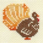 Use variegated thread for feathers, so you're really only using 4 colors. Brown for body, variegated orange for feathers, red and orange for face and feet.
