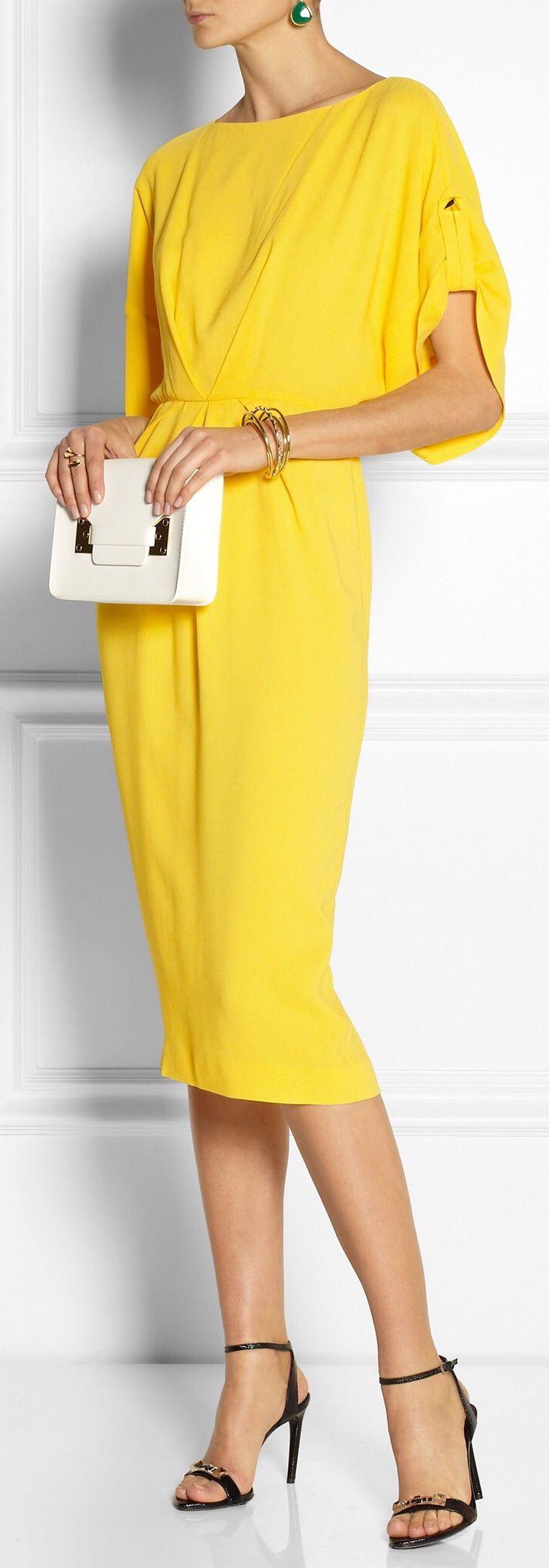 Un amarillo estiloso con unos tacones negros y in bolso blaco con evillas negras