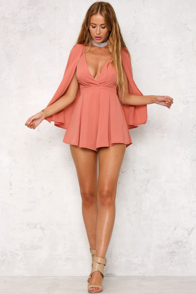 HelloMolly Dark Blush Blissful Evening Playsuit The Blissful Evening Playsuit features an on-trend, cape-style overlaying the sleeveless playsuit. Other details include a deep V neckline, floaty shorts and an invisible zip for easy accessibility. Style yours with black over-the-knee boots for a statement outfit!