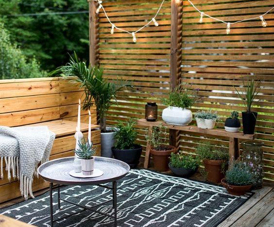 deco terrasse en bois, canapé et brise vue en bois, tapis noir à motifs géométriques blancs, table basse design, plaid gris, plantes vertes, guirlande lumineuse